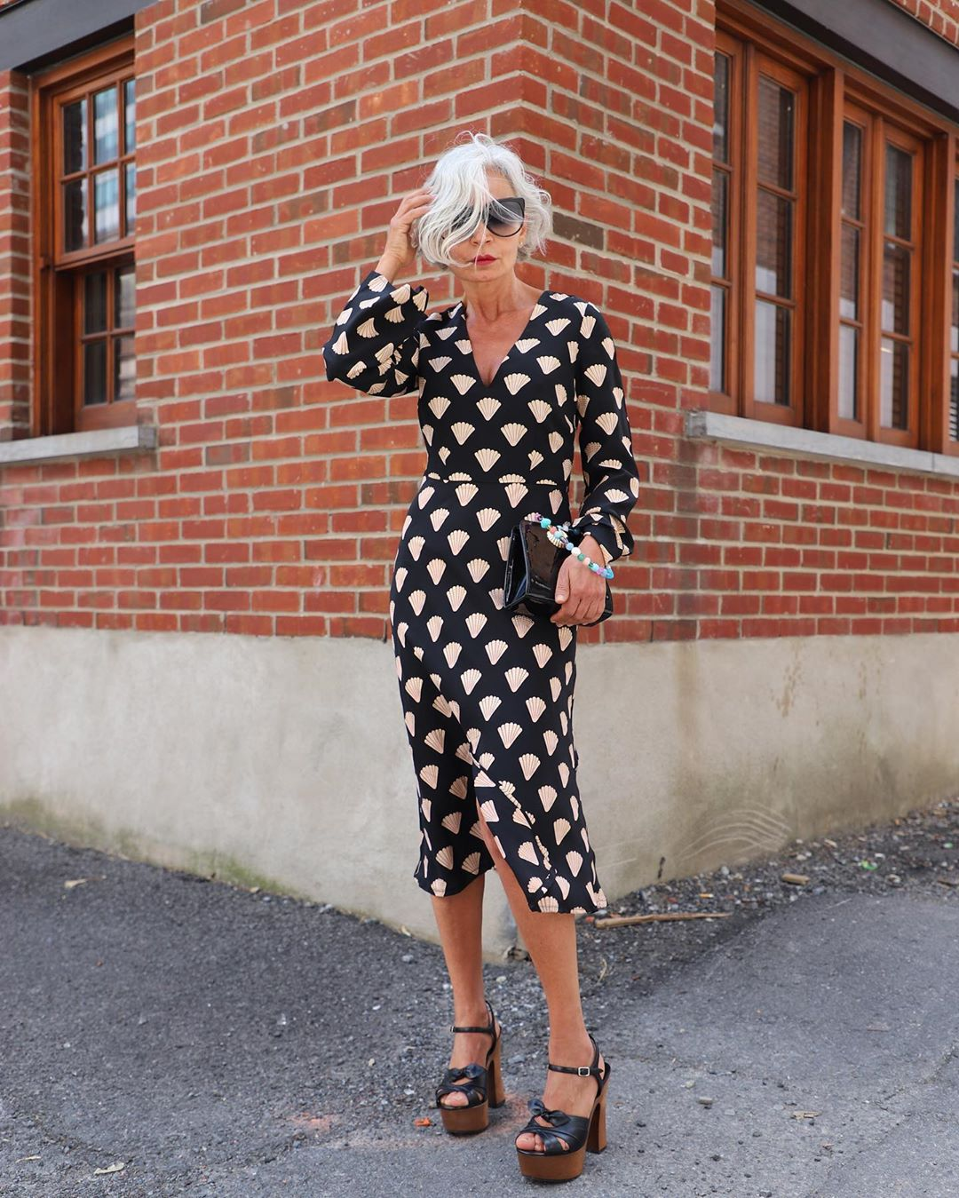Mature classy woman in polka dot dress and gray hair.