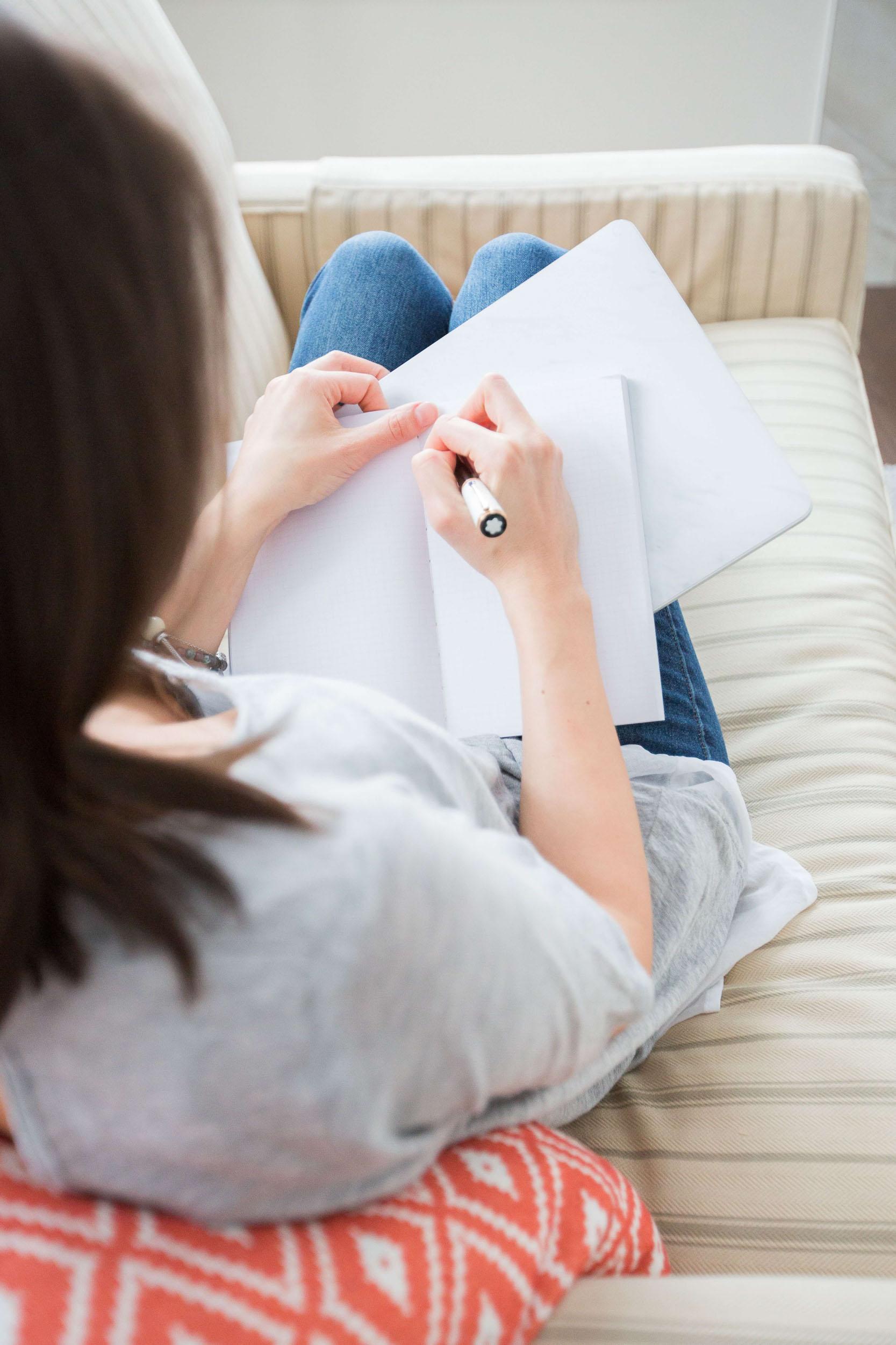 woman starting bullet journal diy planner spread in notebook