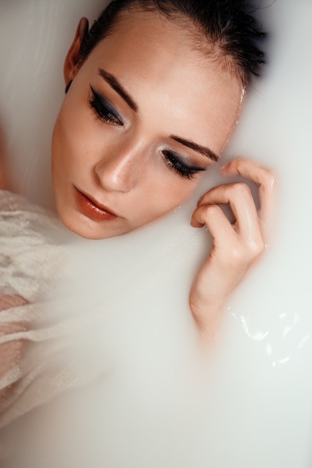 Woman taking milk bath for self care routine